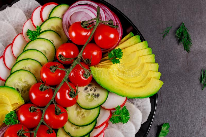 Spring vegetable salad with avocado fresh tomatoes, cucumber, onion tasty healthy food on a gray background, top view royalty free stock photo