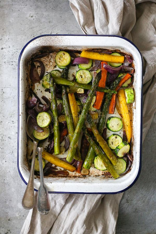 Spring veggies baked and served. In baking tray with two rustic spones stock photos