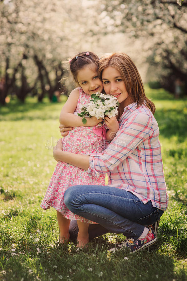 Spring vertical portrait of happy mother and kid daughter stock photography