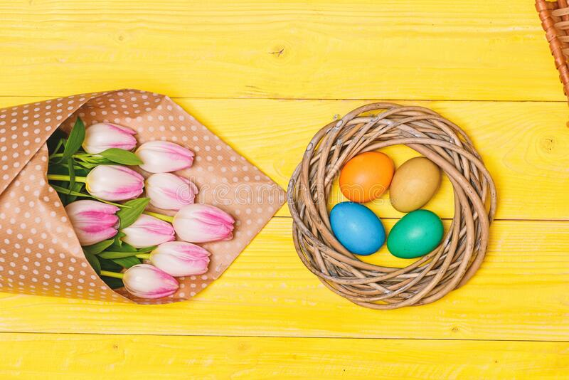 Spring vibes. Colorful bright eggs and bouquet fresh tulip flowers on yellow background top view. Spring holiday. Tradition celebrate easter. Happy easter royalty free stock image