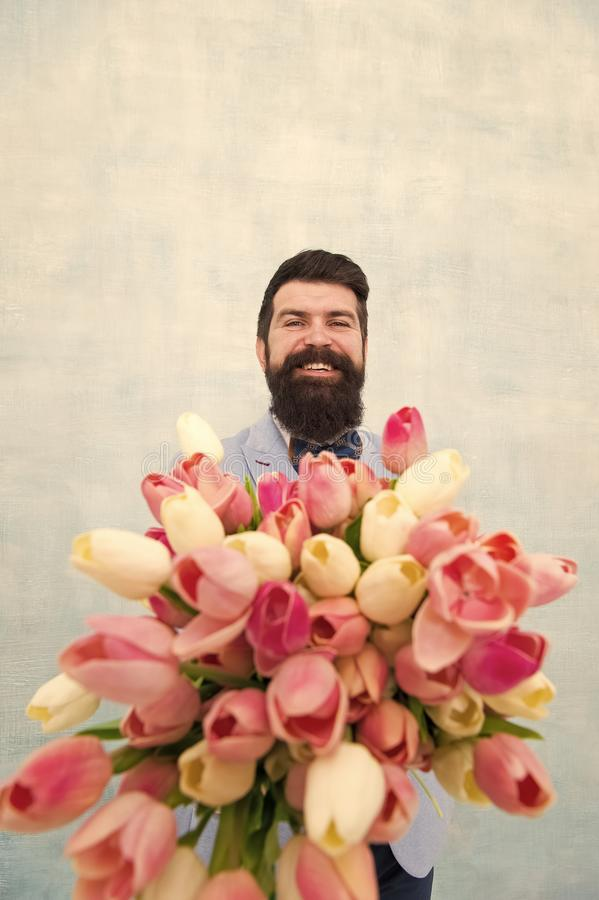 Spring vibes. Gentleman romantic surprise for her. Flowers delivery. Gentleman romantic date. Birthday greetings. Best. Flowers for girlfriend. Man bearded suit stock photos