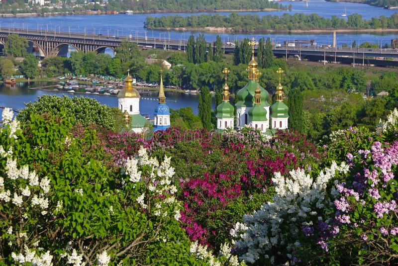 Vydubychi Monastery and Dnipro river in Kyiv, Ukraine. Spring view of Vydubychi Monastery and Dnipro river with pink and white lilac blossoming in the botanical royalty free stock image