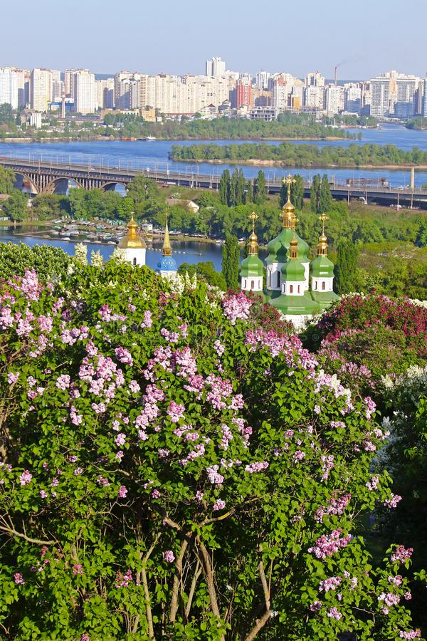 Vydubychi Monastery and Dnipro river in Kyiv, Ukraine. Spring view of Vydubychi Monastery and Dnipro river with pink and white lilac blossoming in the botanical stock photo