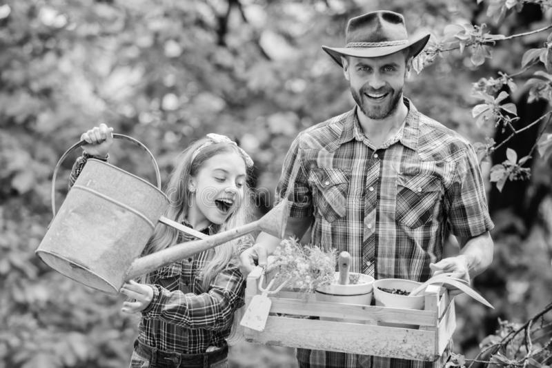Spring village country. little girl and happy man dad. earth day. ecology. Watering can and shovel. family farm. father stock image