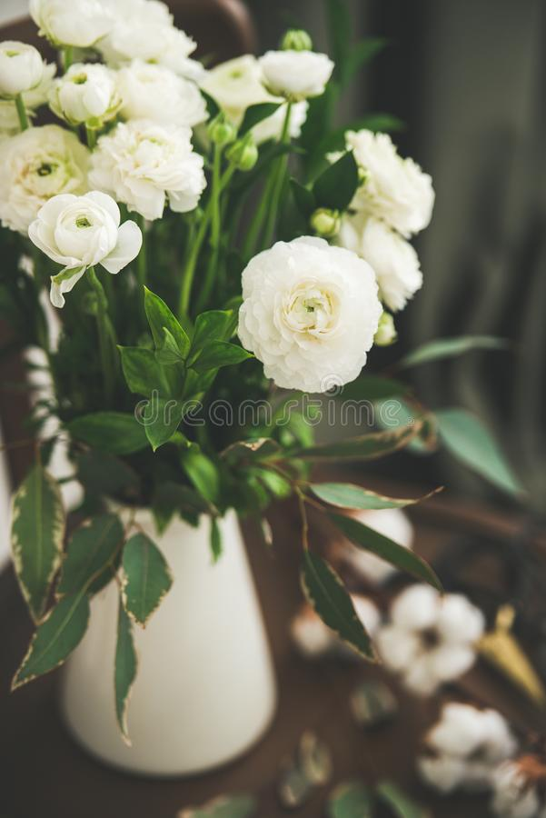 Spring white buttercup flowers in enamel jug with curtain behind. Spring white buttercup flowers in white enamel jug on wooden vintage chair with curtain behind stock images