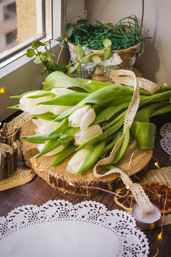 Spring white tulip on the celebrate. On the brown wooden backdround, yellow lights, white lace stock photography