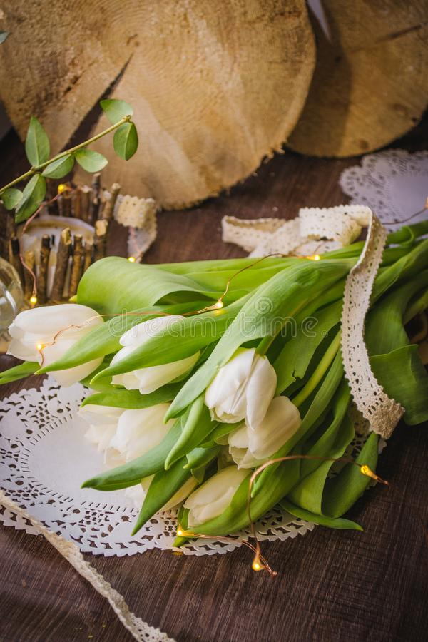 Spring white tulip on the celebrate. On the brown wooden backdround, yellow lights, white lace stock photo
