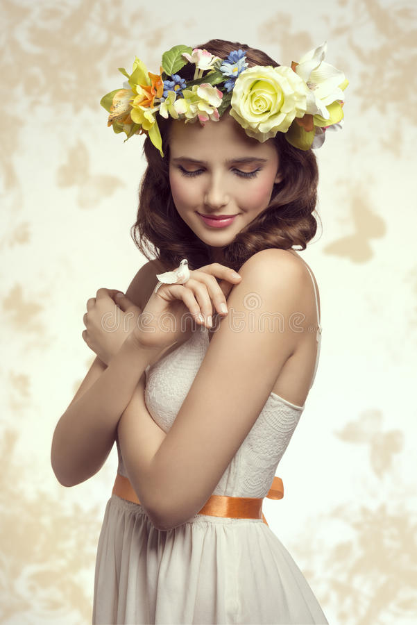Spring woman. Attractive, brunette spring woman in white dress. She has got little bird on her finger and wreath of flowers on her head royalty free stock images