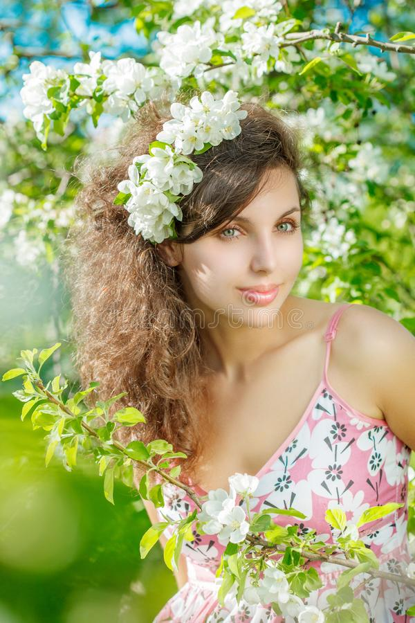 Spring Woman.Beautiful Girl model with spring flowers. Young Fem. Ale with blooming apple and cherry on the background of a summer garden. Allergy to pollen royalty free stock image