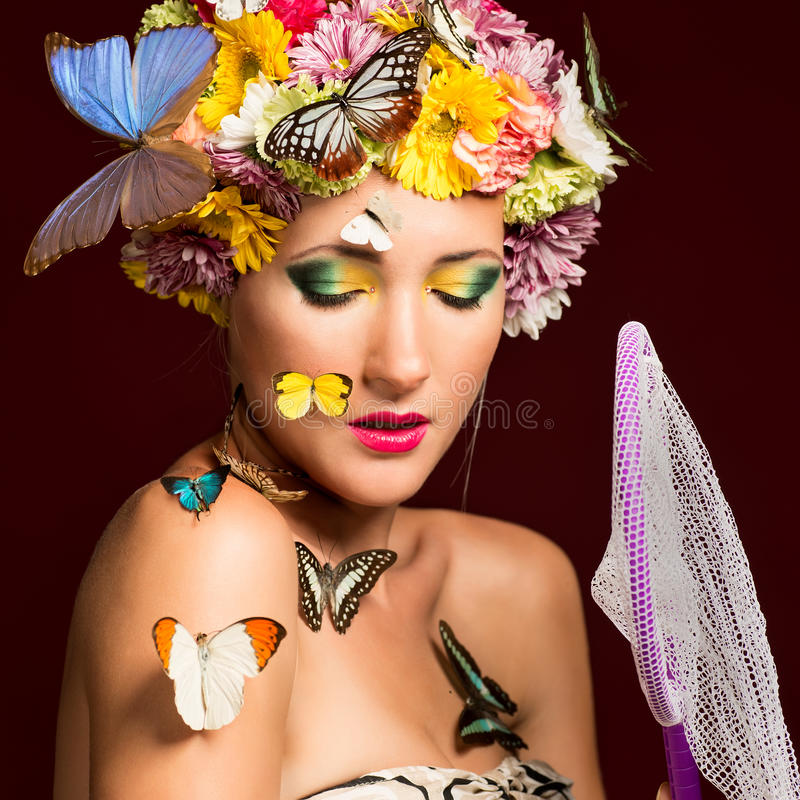 Spring woman with butterflies and flowers stock images