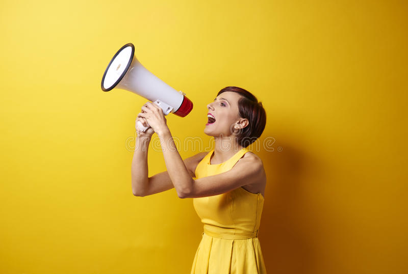 Spring woman. Female model using bullhorn in photo session royalty free stock photo