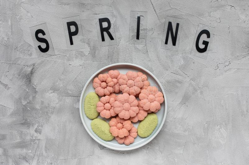 SPRING word and flower cookies on a plate on a gray background . Spring holidays cooking concept. Top view, flat lay, copy space stock photo