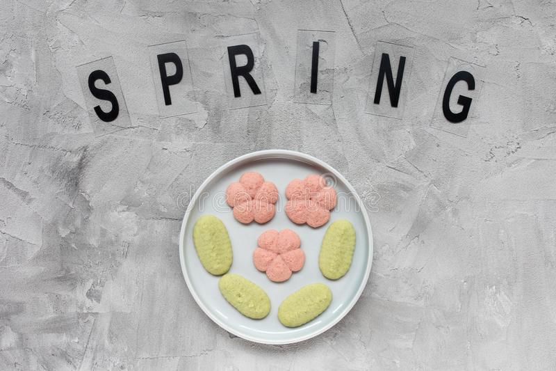 SPRING word and flower cookies on a plate on a gray background . Spring holidays cooking concept. Top view, flat lay, copy space royalty free stock photo