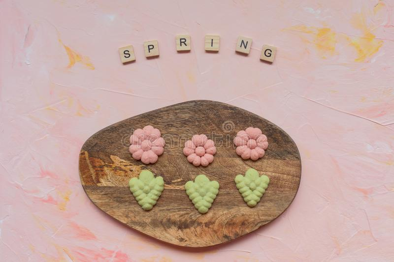 SPRING word and flower cookies on a wooden board on a pink background . Spring holidays cooking concept. Top view, flat lay royalty free stock images