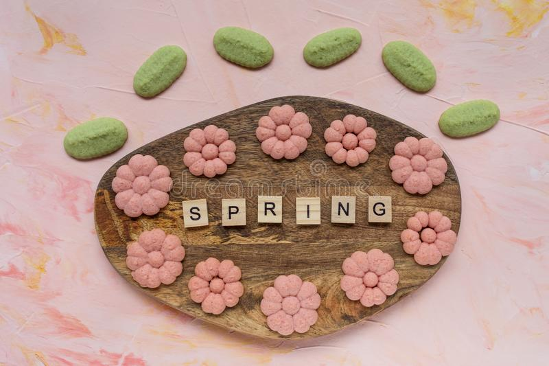 SPRING word and flower cookies on a wooden board on a pink background . Spring holidays cooking concept. Top view, flat lay stock image