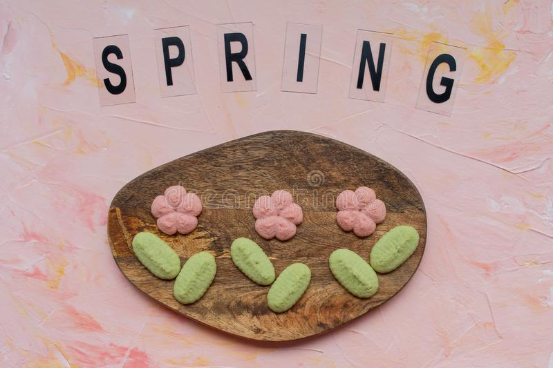 SPRING word and flower cookies on a wooden board on a pink background . Spring holidays cooking concept. Top view, flat lay royalty free stock photo