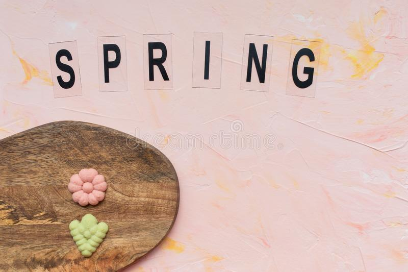 SPRING word and flower cookies on a wooden board on a pink background . Spring holidays cooking concept. Top view, flat lay, copy space royalty free stock photo