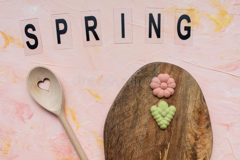 SPRING word, stirring spoon and flower cookies on a wooden board on a pink background . Spring holidays cooking concept. Top view, flat lay stock photos