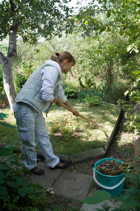 Spring works in the country. Cleaning old leaves royalty free stock photos