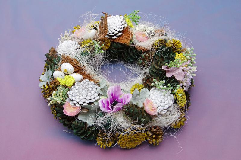 Spring wreath on ultra violet background. Wreath made of natural materials. The main materials are cones, sisal. Cones are painted with colors in yellow, white stock photography