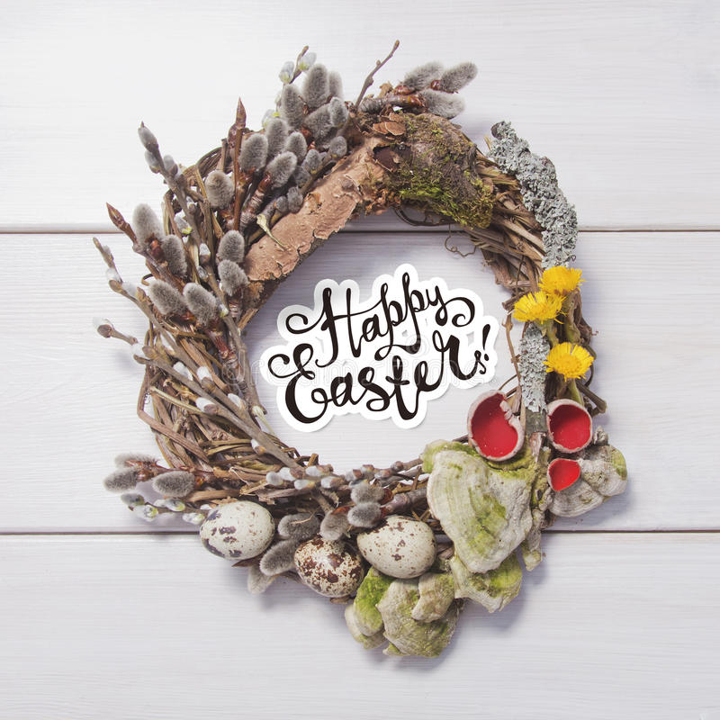 Spring wreath on a white wooden background. Happy Easter card . Wreath with willow twigs; mushrooms and quail eggs on a white wooden background royalty free stock photos