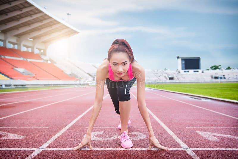 Springa den färdiga och säkra kvinnan i startande position royaltyfria bilder