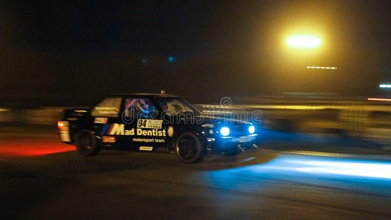 Springa för BMW M3 sportar trimmat bil på den Chayka strömkretsen, nattlopp som är snabbt med rörelsesuddighet, billyktor på, Kyi royaltyfri foto
