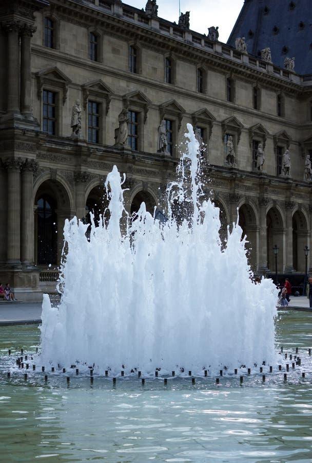 Springbrunn framme av Louvreslottmuseet, Paris, Frankrike, Juni 25, 2013 arkivbilder