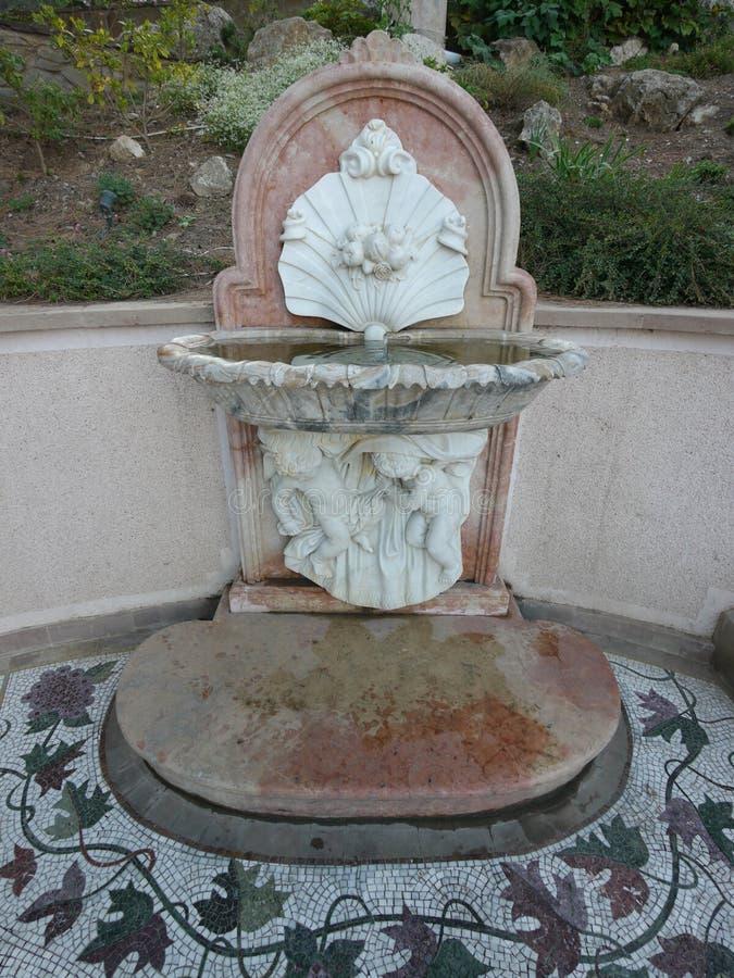 Springbrunn i form av två änglar som rymmer en trumpetsnäcka med pärlor royaltyfri foto