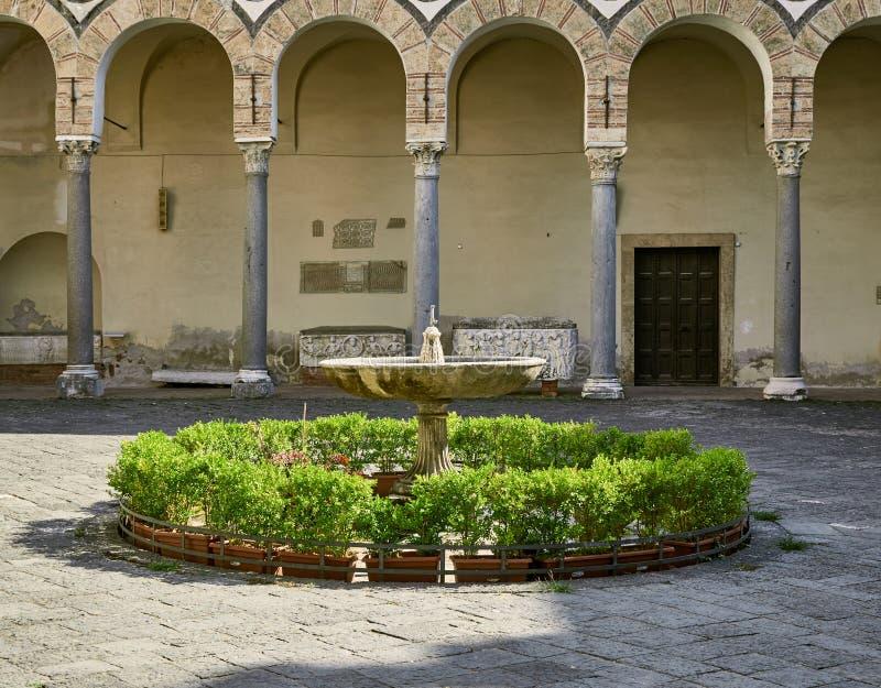 Springbrunn med blommor i uteplatsen av duomoen i Salerno royaltyfri bild