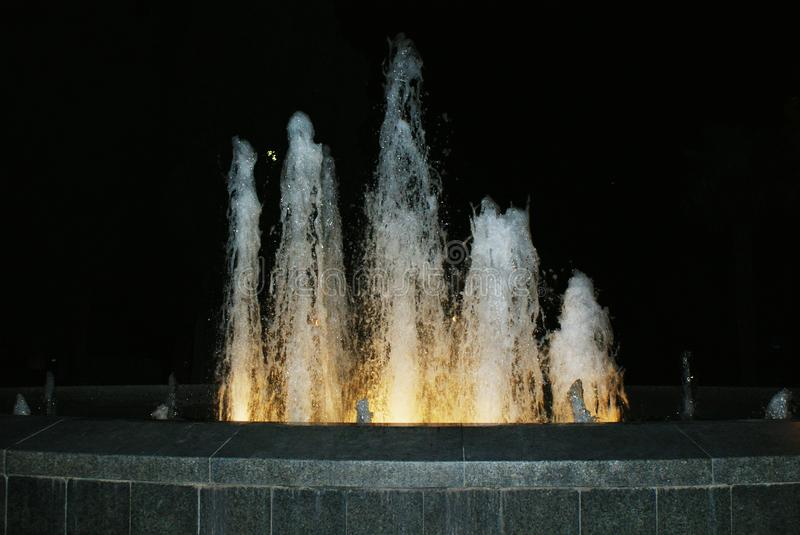 Springbrunn med fem vattenstrålar på natten arkivbild