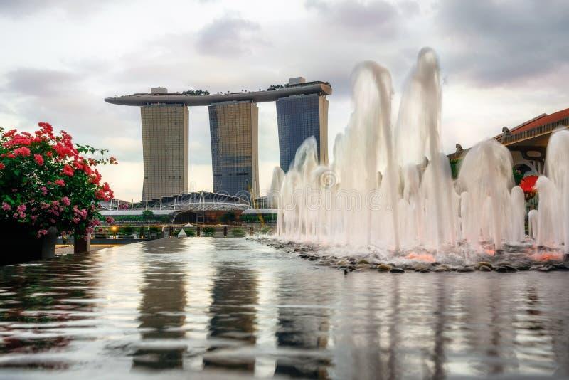 Springbrunn mot det Marina Bay Sands hotellet på solnedgången i Singapore royaltyfri fotografi