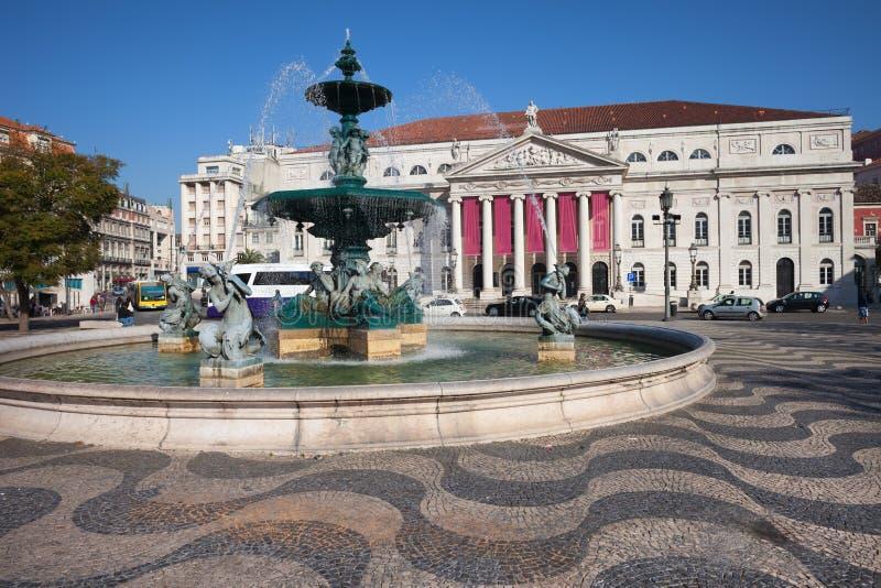 Springbrunn och teater på den Rossio fyrkanten i Lissabon royaltyfri foto
