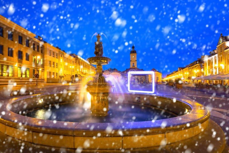 Springbrunn på den huvudsakliga fyrkanten av Bialystok på natten med fallande snö royaltyfria bilder