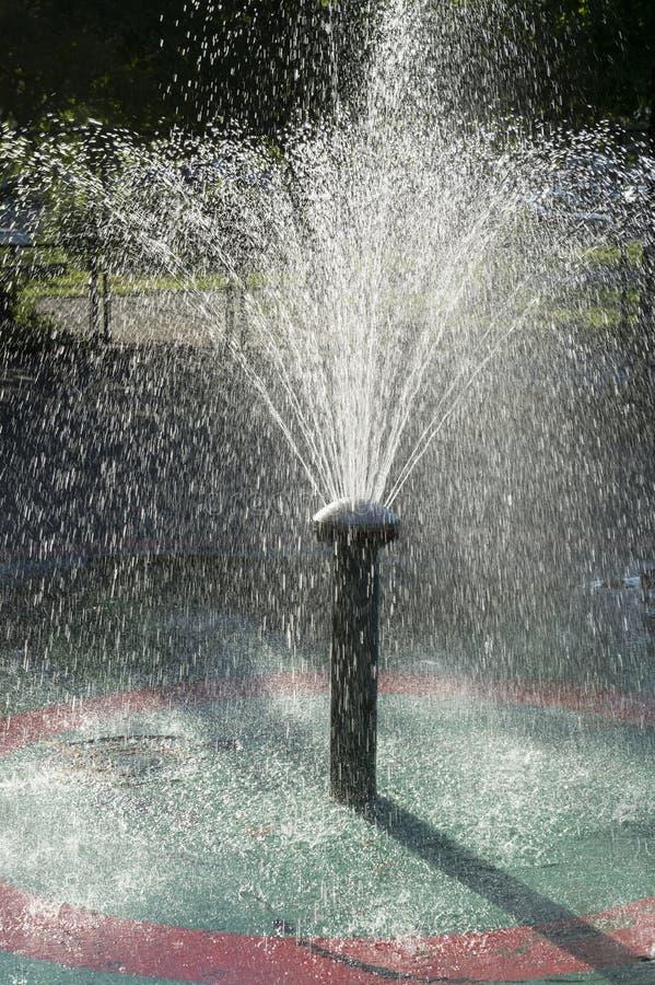 Springbrunn som besprutar vatten Backlit av solen arkivfoton