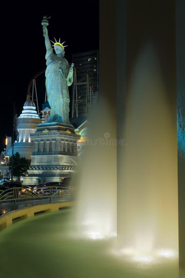 Springbrunnarna för MGM-hotellvatten tänder upp den Las Vegas remsan, tillsammans med en staty av frihetkopian royaltyfri foto