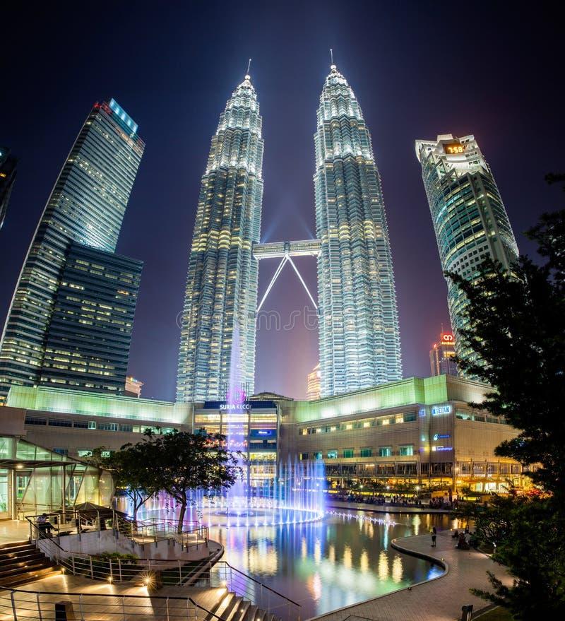 Springbrunnshow på natten framme av Petronas tvillingbröder royaltyfri fotografi
