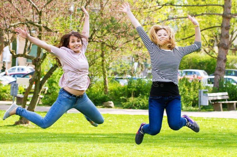 Springen der jungen Frau zwei stockbild