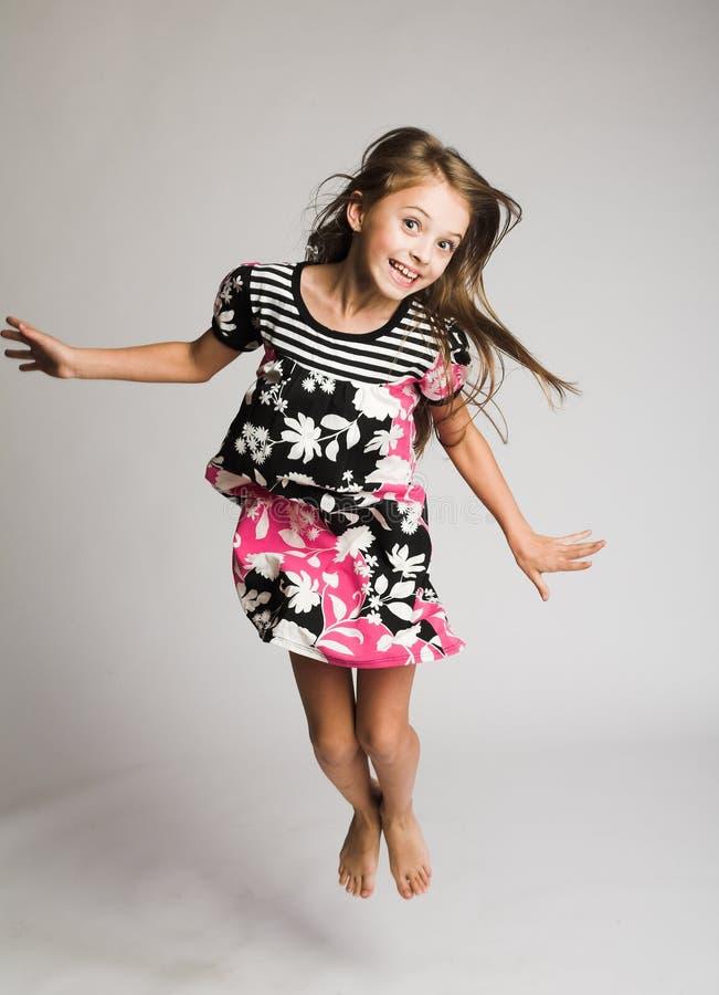 Springen des kleinen Mädchens der Freude stockbild