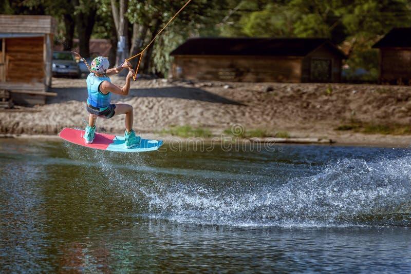 Springen Sie über das Wasser auf einem wakeboard stockfotografie