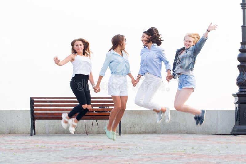 Springen Sie oben für Freude Beste Freunde haben Spaß im Park stockbild