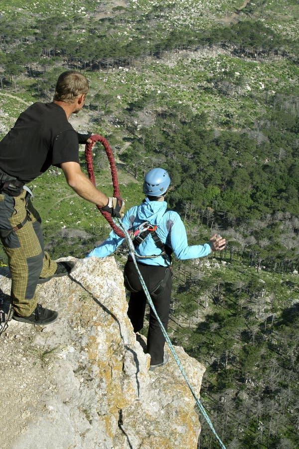 Springen Sie weg von einer Klippe mit einem Seil Aufgeregtes kleines Mädchen lizenzfreie stockfotos