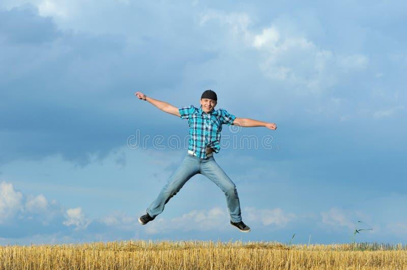 Springen van de jongen, die tegen blauwe hemel loopt royalty-vrije stock foto