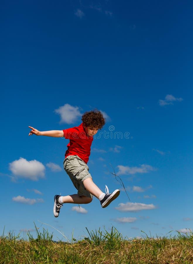 Springen van de jongen, die tegen blauwe hemel loopt stock afbeelding