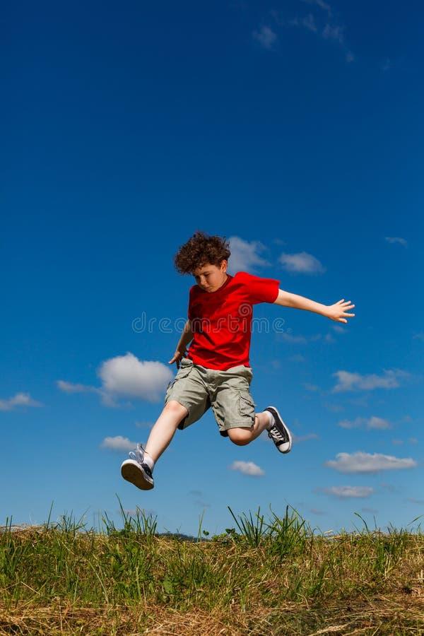 Springen van de jongen, die tegen blauwe hemel loopt royalty-vrije stock afbeeldingen
