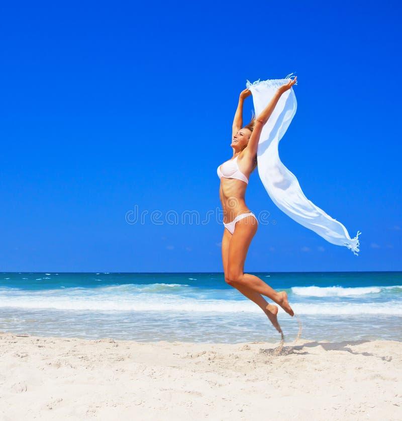 Springend gelukkig meisje op het strand royalty-vrije stock fotografie