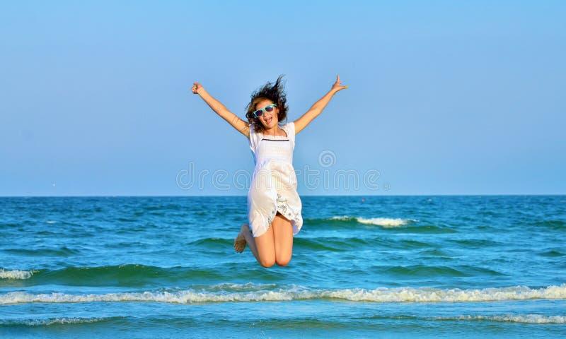 Springend gelukkig meisje op het strand stock afbeelding