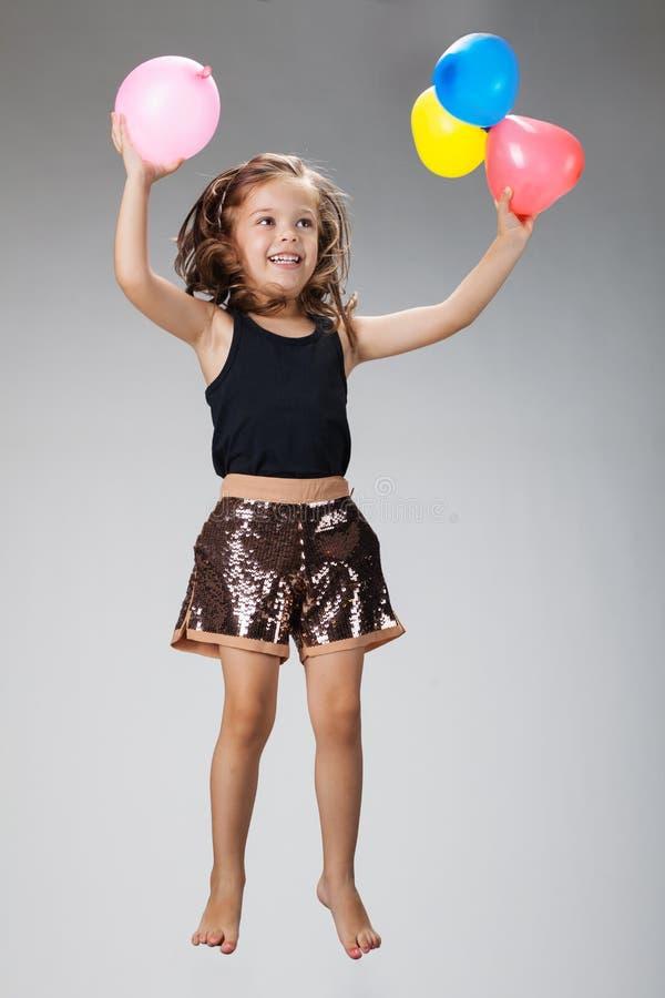 Springend meisje met ballons royalty-vrije stock afbeeldingen
