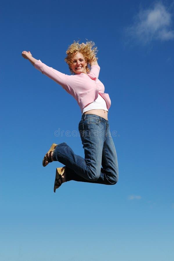 Springende Frau an einem sonnigen Tag stockfotos