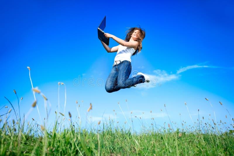 Springende Frau mit Laptop stockfotos